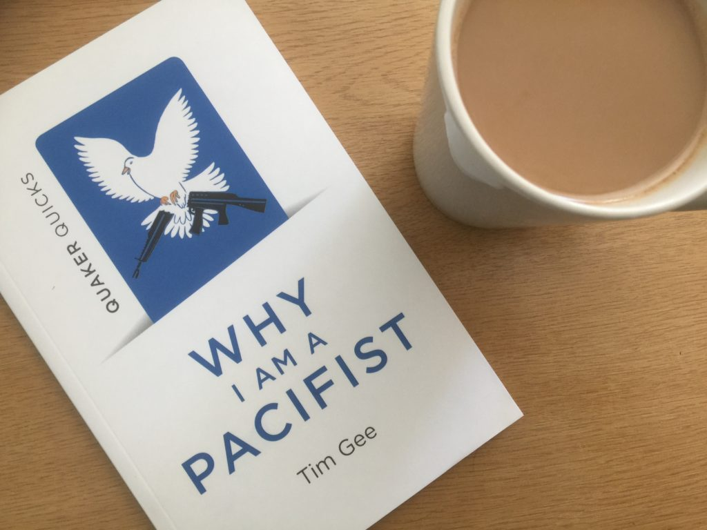 A white book, titled 'Why I Am A Pacifist' is on a brown table beside a cup of coffee